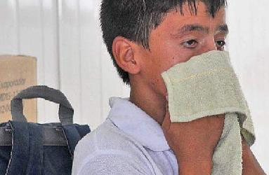 Un niño se limpia el sudor en un aula