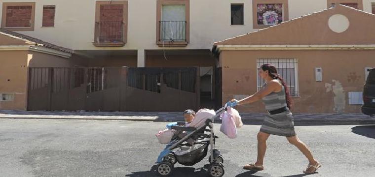 Una joven pasea a su hija por la calle 28 de Febrero, donde se sitúan las viviendas ocupadas