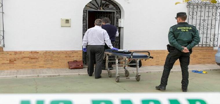 Miembros de los servicios funerarios se dirigen a la vivienda de la localidad sevillana de Aznalcóllar donde esta tarde ha sido encontrado el cuerpo sin vida de una mujer de 80 años con indicios de violencia. / EFE