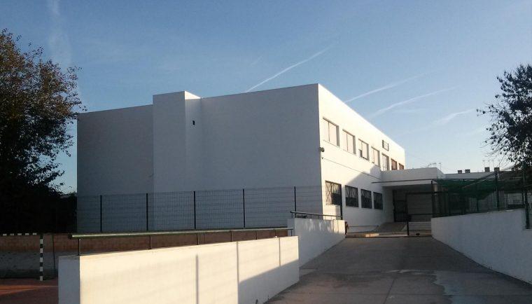 Arriba la fachada del colegio Pío XII de Carrión de los Céspedes. A la izquierda una de las aulas del centro. En la fotografía se puede observar que el techo tiene un gran desconchón debido al mal estado de las cubiertas del edificio