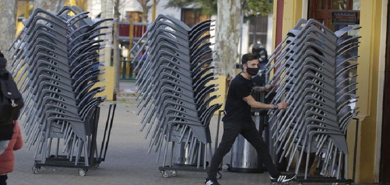 Un camarero apila las sillas al llegar la hora de cierre / JUAN CARLOS MUÑOZ